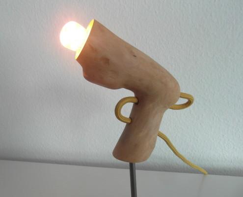 5/6 De fitting is in het hout gezet en het snoer is zo door het hout geleid waardoor het idee van een lichtpistool duidelijker wordt