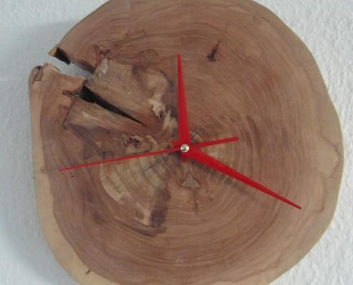De rode wijzers passen erg mooi bij de kleuren van het hout