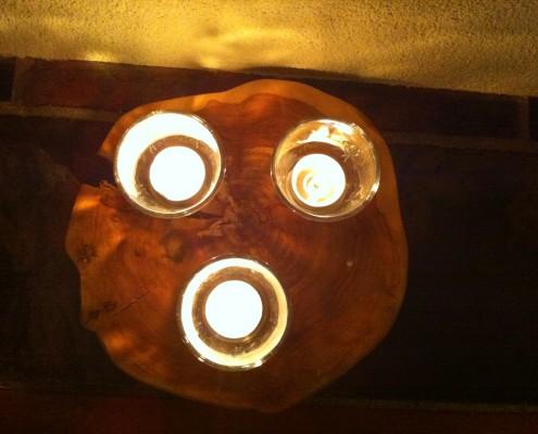 Een klant heeft drie waksienelichtjes op een schijf van appelhout geplaatst