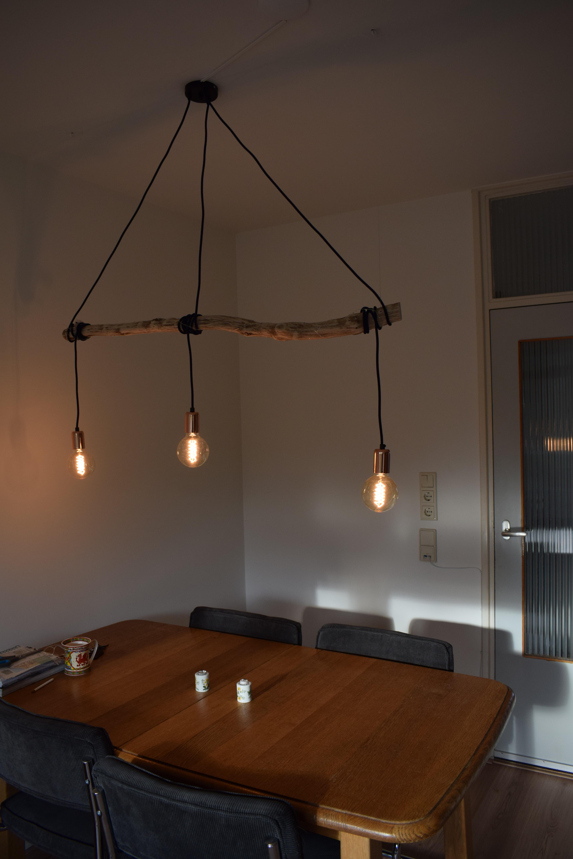 Als je goed kijkt zie je de mooie kleuren en structuren van het hout verlicht worden door de drie lampen